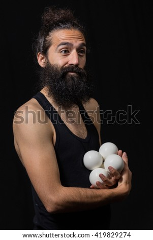 Happy circus juggler with his balls miming during a performance - stock photo