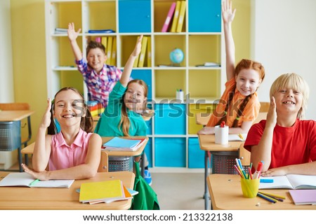 Happy classmates raising hands at lesson - stock photo