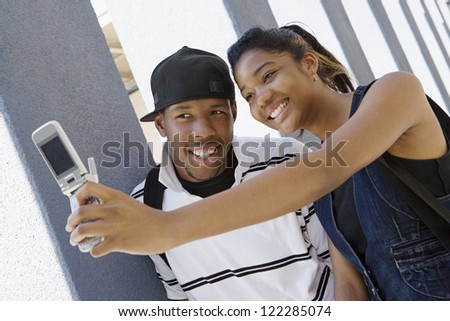 Happy classmates self photographing in college corridor - stock photo