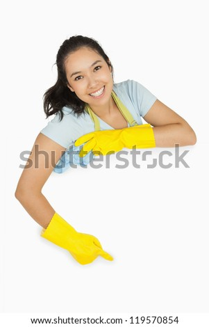 Happy cleaning lady in rubber gloves and apron pointing to white surface - stock photo