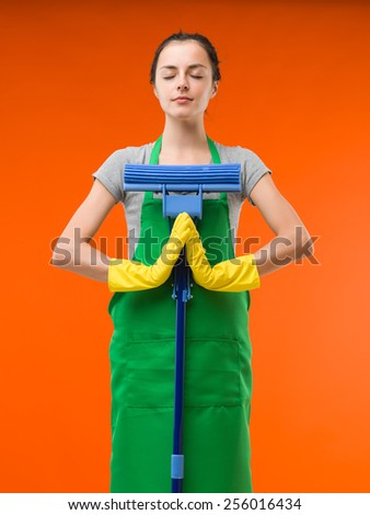 happy cleaning lady meditating while holding mop, on orange background - stock photo
