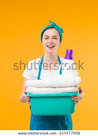 happy cleaning woman holding basin with clean towels and detergent, on yellow background - stock photo