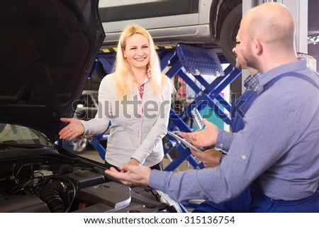 Happy client at a repair shop smiling in front of mechanics and pointing her hand to the engine bay
