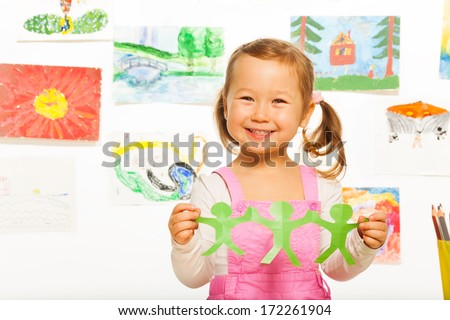 Happy close portrait of smiling Asian girl holding paper green mans cut out - stock photo