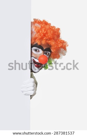 Happy clown hiding behind billboard over white background