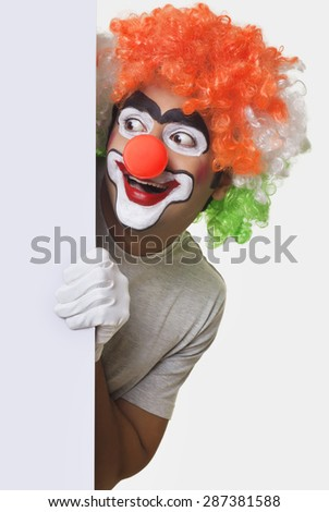 Happy clown staring at something while hiding behind whiteboard - stock photo