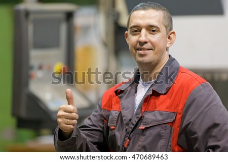 Happy CNC lathe worker gesturing ok at factory workshop background