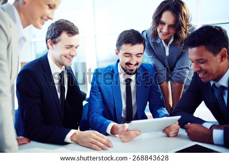 Happy co-workers looking at data in touchpad - stock photo