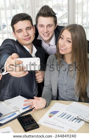 Happy co-workers makes selfie. Three laughing young business people makes SELFIE with the sell phone. Office interior, stationery, paper, charts on the table - stock photo