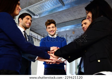 Happy co-workers making pile of hands - stock photo