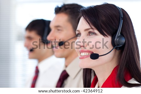 Happy co-workers with headsets on in call center - stock photo