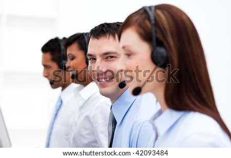 Happy co-workers with headsets on working in call center. Business concept.
