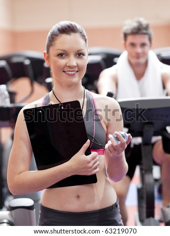 Happy coach measuring time with a chronometer while man is doing exercises in a sport centre - stock photo