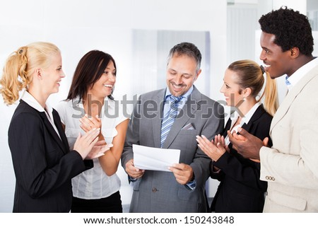 Happy Colleagues Applauding Businessman Holding Paper In Office - stock photo
