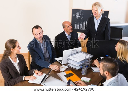 happy colleagues discussing price development at office - stock photo