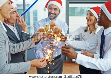 Happy colleagues in Santa caps having Christmas fun while toasting with champagne at party in office - stock photo