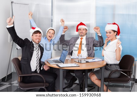Happy Colleagues In Santa Hat Celebrating Christmas At Office - stock photo