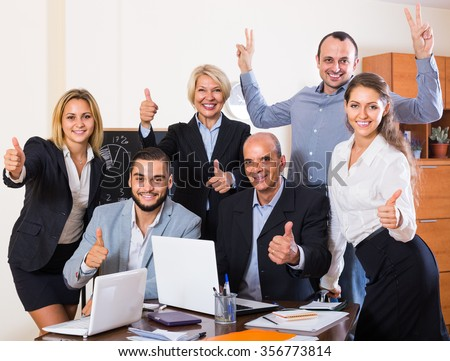 Happy colleagues looking at laptop and smiling - stock photo