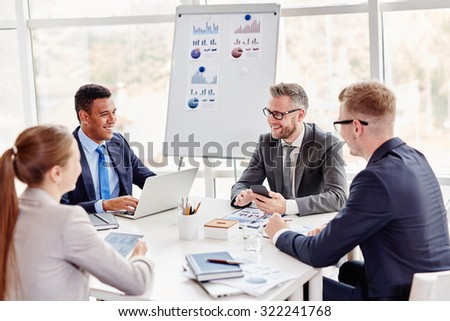 Happy colleagues voicing and discussing their ideas at meeting - stock photo