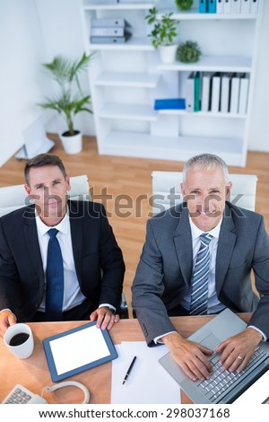 Happy colleagues working together on digital tablet and laptop in the office - stock photo