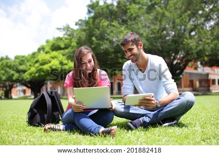 Happy College students using laptop and tablet pc on campus lawn, caucasian - stock photo