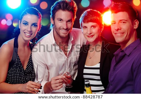 Happy companionship drinking, smiling in discotheque.?