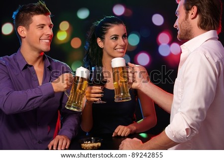 Happy companionship having fun in nightclub, clinking glasses, smiling.? - stock photo