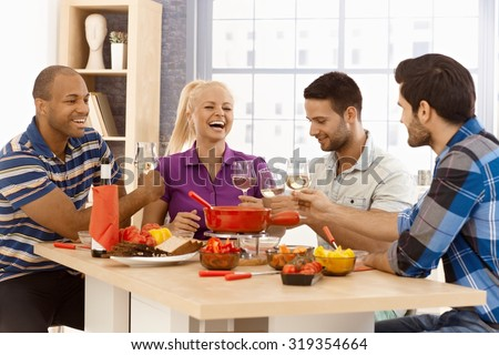 Happy companionship sitting around table at home, having cheese fondue, clinking glasses. - stock photo