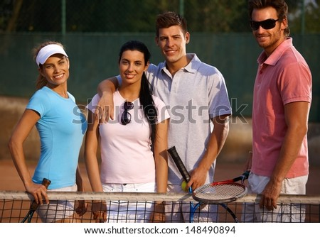 Happy companionship standing on tennis court, smiling. - stock photo