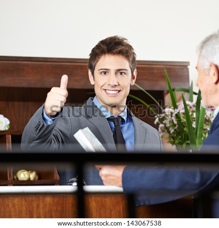 Happy concierge in hotel at reception showing his thumbs up - stock photo
