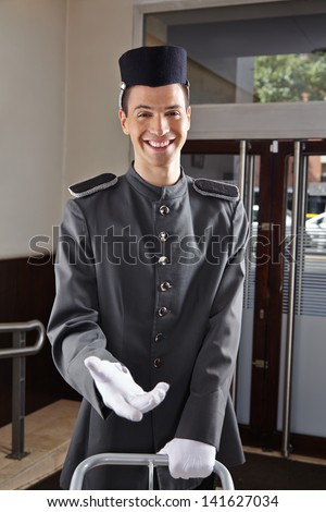 Happy concierge in uniform standing in a hotel lobby - stock photo
