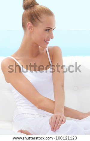 Happy confident beautiful woman smiling broadly and looking off camera while seated on a white couch - stock photo