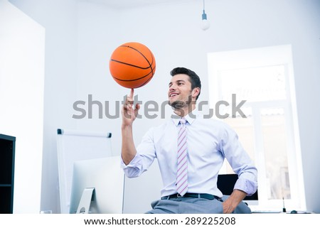 Happy confident businessman spining ball in office - stock photo
