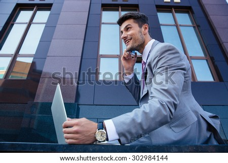 Happy confident businessman talking on the phone and using laptop outdoors. Looking up - stock photo