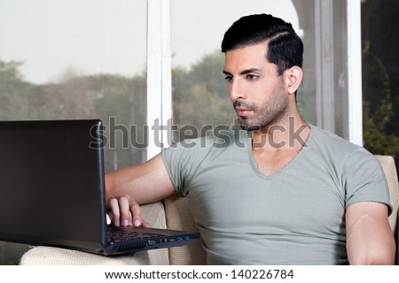happy confident man using laptop and sitting on the sofa - stock photo