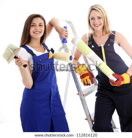 Happy confident woman decorators Two happy confident woman decorators posing with their equipment for a wallpapering project on a white background - stock photo