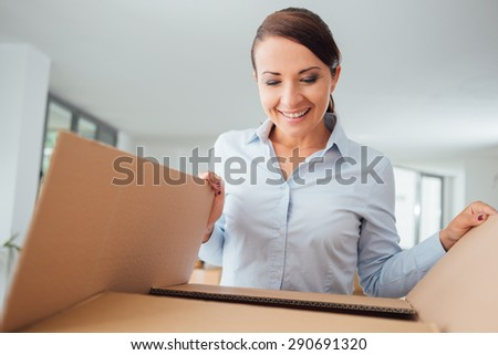 Happy confident woman unpacking and moving into her new office, she is opening a cardboard box and looking into it - stock photo
