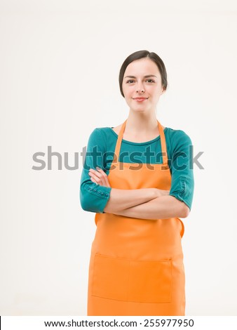 happy confident woman wearing orange apron on white background - stock photo