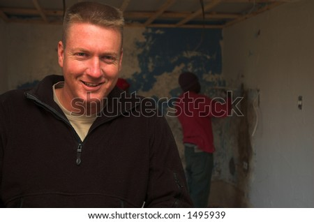 Happy construction foreman with workers in background - stock photo