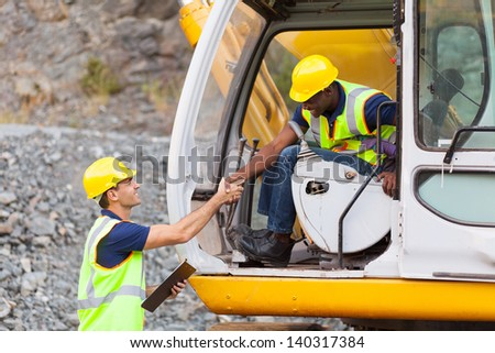 happy construction manager handshaking with bulldozer operator at construction site - stock photo