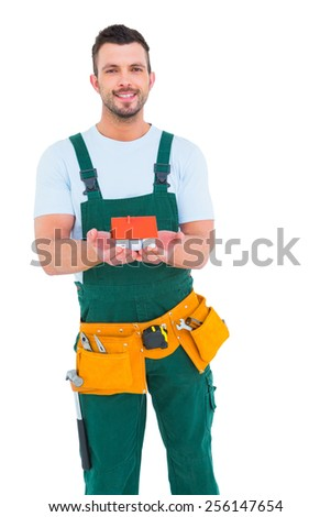 Happy construction worker holding house model on white background - stock photo