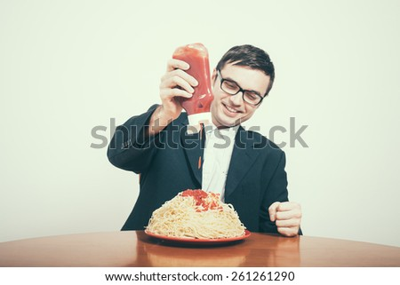 Happy consumerism concept. Happy businessman pouring ketchup on huge dish of pasta. - stock photo