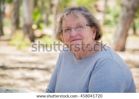 Happy Content Senior Woman Portrait Outdoors At Park. - stock photo