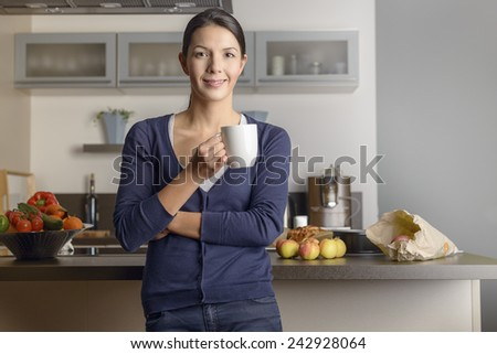 Happy contented housewife in her kitchen giving the camera a warm friendly smile as she relaxes with a mug of coffee with fresh fruit on the counter behind her - stock photo