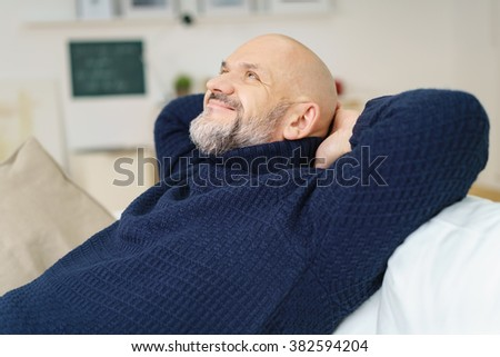 Happy contented middle-aged man with a goatee relaxing at home on the sofa with his hands behind his head smiling with pleasure as he looks up into the air - stock photo
