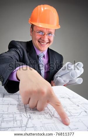 Happy contractor in hardhat pointing to plans - stock photo
