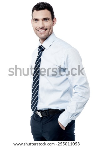 Happy corporate man posing with hands in pockets