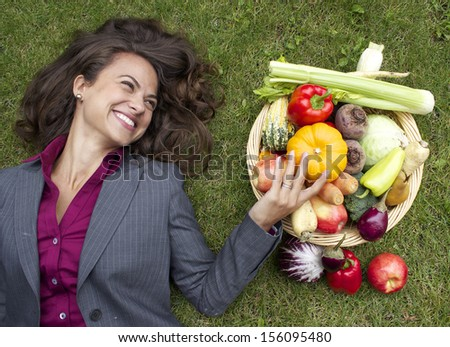 happy corporate woman lying on grass next to vegetable basket