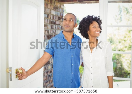 Happy couple about to open the door of their house - stock photo