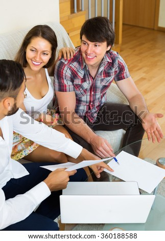 Happy couple and salesman talking cheerfully about purchase in living room - stock photo